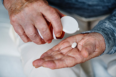 Elderly taking a pill bought from online canadian pharmacy
